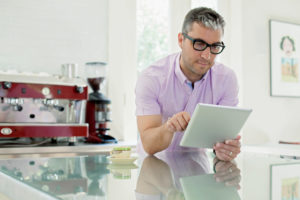 Portrait of man using digital tablet in domestic kitchen