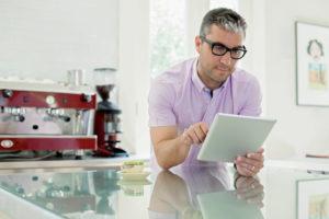 Portrait of man using digital tablet in domestic kitchen
